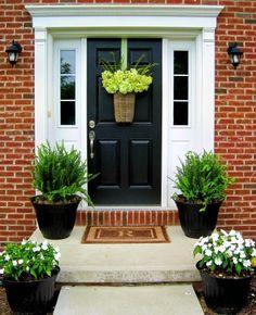 Black door, white trim, red brick house.