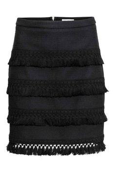 Jupe avec galon pompons: Jupe courte en coton tissé légèrement texturé. Modèle avec quatre rangs de galon pompons décoratif. Fermeture à glissière apparente dans le dos. Non doublée.