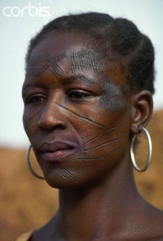 Africa | A Bobo woman displays tribal scars on her face in Burkina Faso. |  © Charles & Josette Lenars