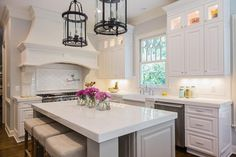 A pair of round black lanterns illuminate a gray kitchen island with chunky legs topped with thick white quartzite lined with gray microfiber backless counter stools.