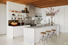 """The sleek, minimalist kitchen of author/photographer Kelly Klein complements the open and airy design of her Palm Beach, Florida, house, which was created by David Piscuskas of the firm 1100 Architect. """"Some people don't like looking at their things,"""" Klein says of her kitchen's shelving. """"I like seeing my glassware and dishes."""" (August 2012)"""