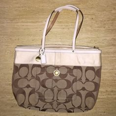 """PRICE DROP! AUTHENTIC Coach Signature Tote PRICE DROP! AUTHENTIC Coach Tan & White Signature Tote Purse  Excellent condition! Very minor wear under handles as shown in the picture. 2 small pockets and one large zippered pockets inside and one pocket outside. ~16"""" long x 9.5"""" tall x 5"""" wide. Model # A0867-11691.  Any questions? Just ask!  Smoke- & pet-free home  No returns, trades or low balling please!  Will consider reasonable offers!  15% off 2+ items! Coach Bags Totes"""
