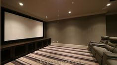 Media room with custom hand built cabinets.  Cabinet doors have speaker mesh for panels allowing the audio gear to vent and stay cool.