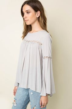 Solid bell sleeve tunic top with trimming all around and button closure keyhole at back. Content + Care: 100% Rayon Hand Wash