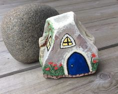 Painted rock fairy gnome elf house for a fairy garden with the natural color of the stone showing through in the background.