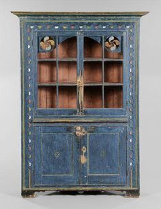 attributed to the Ralph family of cabinet makers, Sussex County, Delaware, 1800-1820, poplar and pine, single-case construction, two glazed doors with interior valance with pierced fylfot spandrels and polychrome decoration over two paneled doors, original cornice and feet, all with remarkable original blue, yellow, red and white paint decoration, undisturbed backboards with cut nails, 77-1/2 x 55-1/2 x 23-1/2 in., excellent condition overall with original dry painted surface,
