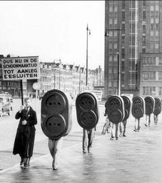 """G.E.B. promotie ter aanschaf van veilige stopcontacten. Rotterdam 17-3-1939. Foto toont sandwichmannen (reclamelopers) die verkleed als stopcontacten in een lange rij over straat lopen. Voorop loopt man met reclamebord """"Dus nu in de schoonmaaktijd tot aanleg besluiten"""". Op de achtergrond het G.E.B.gebouw"""