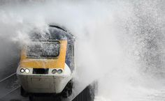 Waves hit a train during heavy seas and high winds in Dawlish in south west Britain