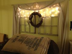 Vintage windows with a grapevine wreath, icicle lights, cotton swag and burlap hearts. The bed features a burlap sack stuff with bed pillows.