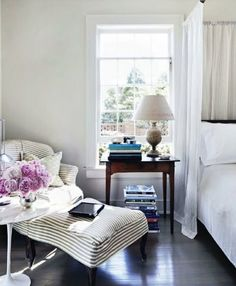 cute part of the bedroom - cosy chair and bedstand with books