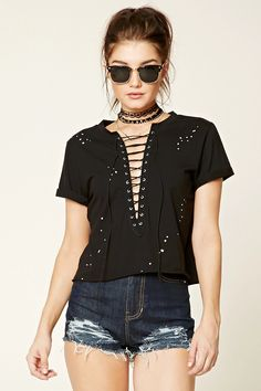 A knit top featuring a pluning lace-up neckline, short cuffed sleeves, metallic polka dots, and a raw-cut hem.