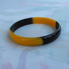 This eye-catching bangle bracelet is molded plastic alternating in butterscotch and dark brown colors. It looks like bakelite, but is lighter in weight and tests negative with Simichrome. The bracelet has a 2-5/8 inch inside diameter, is 1/2-inch wide, and is in excellent vintage condition. It will be shipped in a gift box.  #shopifypicks