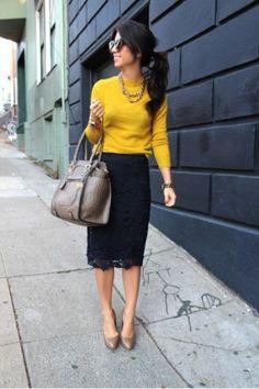 Ella lleva una camisa amarillo y mangas, una falda de encaja, azul y larga, un collar, unas gafas de sol, y tacones cafe. -Madi & Erica