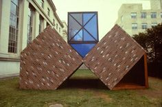 """Vito Acconci """"Bad Dream House"""" (1984) """"Three upside-down houses, fit together to make a multi-part dwelling: two upside-down houses tilted over and propped up against each other, so that they cradle a third upside-down house above."""" Materials: Wood, brick-face, shingles, Plexiglas, screen."""""""