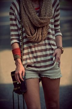 Brown and white striped top with large infinity scarf and light denim jeans paired with gold accent jewelry and stacked bracelet