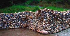 kreative Gartenmauer aus flusssteinen