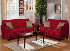 Grey walls and beige accents tone down the red leather sofas.