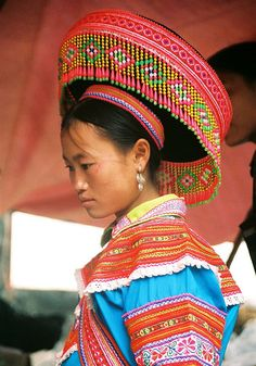 A Flower Hmong woman and her elaborate headdress.   Taken at the weekly market in Xín Mần, Hà Giang. She was a little shy!  This photo was taken during a motorcycle expedition with Explore Indochina. (Photo by Glenn Phillips ~ May 29, 2005)