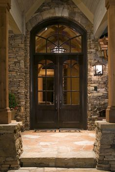 This beautifully sculpted home exterior is highlighted with stone surroundings, vaulted entry ceiling, a double door entry, wood and glass front doors and wood columns around the entry. Not many homeowners concentrate on their front entry, but when you do, it assuredly adds to the curb appeal like it has here.