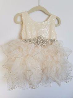 Beautiful ivory sequin bodice with rhinestone belt and layered tulle bottom. Perfect for flower girls, baptisms, birthdays, weddings, photos,church and more. - Fully lined. - Cotton / Polyester - Hand