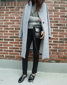 Simple elegance: straight black trousers, light grey jumper and light grey coat.