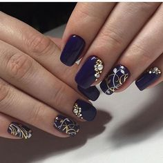 Sophisticated looking dark blue nail art design. The nails are painted in dark blue nail polish and have additional elements on top in gold and silver colors. Other embellishments are also added to highlight the nails like silver and gold beads.