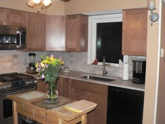 Photo gallery of remodeled kitchen features CliqStudios Rockford Painted Linen cabinets with bumped out cabinets for built-in furniture style