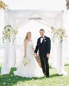 A birch gazebo with sheer, white draping pulled back like curtains on all sides with nautical rope knots will be at the forefront of the ceremony site