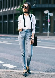 A skinny ribbon scarf is worn with a white blouse, light-wash denim and loafers.
