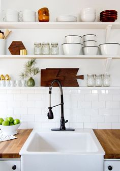 Butcher block counters, apron sink, subway tiles, open shelves.