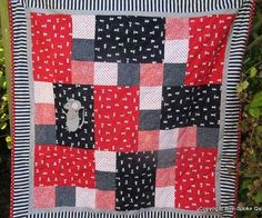"""'Tumbling Mice' Mice are having fun running, skipping, juggling and skateboarding all over this adorable handmade quilt in jolly red and blue. A larger appliqued mouse watches over the little mice, and the spotted and striped fabrics add to the cheerful mood. It is quilted all over with waves and backed with green stripey fabric. It would make a charming play mat or cot quilt. Size:  42"""" x 42"""""""