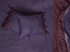 Linen bed sheet set made of three matching violet, eggplant and light purple colors, decorated with pleats. Linen bedding provides year round