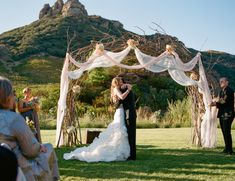 Love the driftwood arch + fabric. It can even do without the flowers!