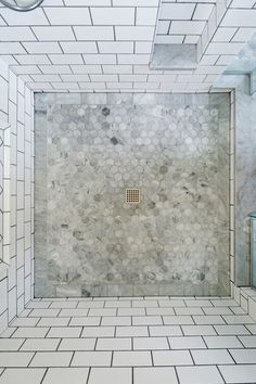 -- if you are doing the tiling yourself, a square drain is much easier to cut around than a round one --The hexagonal tile from the main floor continues into the stall but has a border