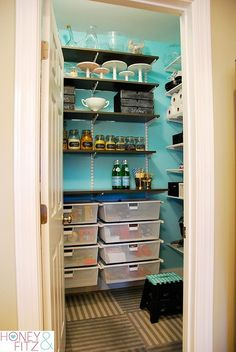 Pantry with fun bright colour contrasted nicely with dark adjustable shelves. Elfa shelving from The Container Store. Drawers are something to consider too. Add some white stenciling (to hide supports) and this would be PERFECT for us!