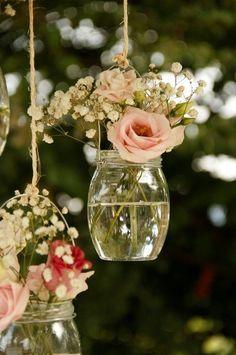 Des vases suspendus avec des bocaux en verre et des anses en fil de fer.
