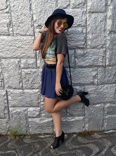 Look do dia com saia plissada, t-shirt amarrada como top cropped, óculos redondo,  chapéu e bolsa cantil.