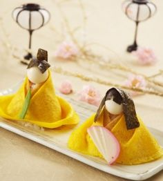 The art of making doll shaped sushi    No instructions (ad for a class) but...make a flavored, triangle rice ball, wrap in a thinly cooked scramble egg sheet, nori and other items for decorations~very simple, delicious treat!
