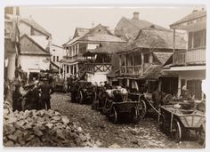 Krzemieniec. Horses and wagons on Broad Street. Half way down the street, laborers are digging up the pavement. 'Look at how the houses are built.'