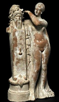 Terracotta figure of Aphrodite crowning a herm of Dionysos with an ivy wreath - 100 BC, circa from Myrina, now British Museum Ancient Greek Sculpture, Ancient Greek Art, Ancient Rome, Ancient Greece, Ancient Goddesses, Greek Gods And Goddesses, Roman Sculpture, Sculpture Art, Aphrodite
