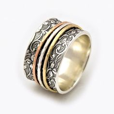 One of the most elegant spinner rings we make, this spinner ring features a leaf motive wide band and three movable bands.  Handmade with care, the leaf motif band features a beautiful pattern that creates a backdrop to the spinner elements.  Each of the spinning bands moves on its own creating an impressive visual for all who see it.  It can be worn on any finger and with just about any outfit. Nature Inspired A truly unique and beautiful spinner ring.    Here you can find more silver and…