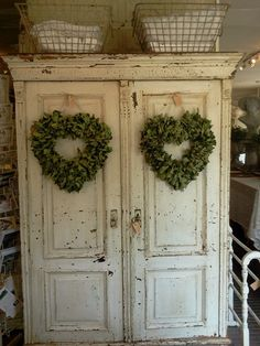 Old White Farmhouse Cupboard...with herb heart wreaths.
