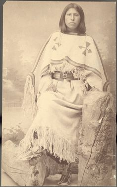 Studio portrait of a young Wind River Shoshone woman wearing a beaded hide dress and moccasins 1883