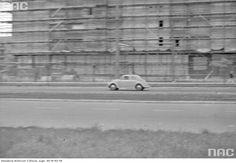 Samochód Volkswagen Garbus na jezdni. W tle budowany blok mieszkalny.
