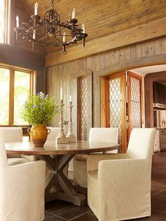 Architectural elements, such as these wood-paneled walls and ceiling, are a substantial way to create the aged Tuscan ambience in a room. You can also enhance the look with decorative elements. The candlestick-style chandelier and leaded-glass door panels add old-world character.