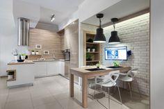 W tej kuchni sterylną biel zestawiono z wysoką zabudową w kolorze kawy z mlekiem, piaskową cegłą na ścianie oraz delikatnymi szarymi detalami w postaci cokołów zabudowy kuchennej. Fot. Pracownia Mebli Vigo, kuchnia Sonomai.