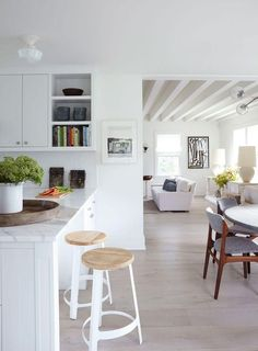 Designer James Huniford transforms a 1910 farmhouse into a contemporary home that's at once intimate and inviting. Love this open plan kitchen and dining room that flows into the living room, all done is neutral whites, grays and wood tones.