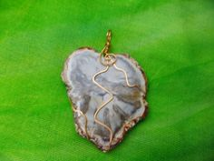 Polished Petrified wood slab wrapped in bronze wire, from base of the stone to the top of the string loop is approx. 2.5 inches. Comes with loose cord. Put in a mesh bag to protect the stone, to be worn as a necklace.