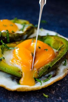 Eggs Baked in Avocado served on a naturally formed white plate. No oven needed! The yolks are perfectly soft unlike the oven baked versions. | giverecipe.com