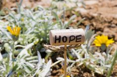 DIY garden markers made with wine corks. All you need are skewers, wine corks, and some twine or ribbon. Use a permanent marker to write inspiring words or the names of what you planted.